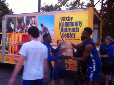 TU football and basketball players help load food donations for the BOC.