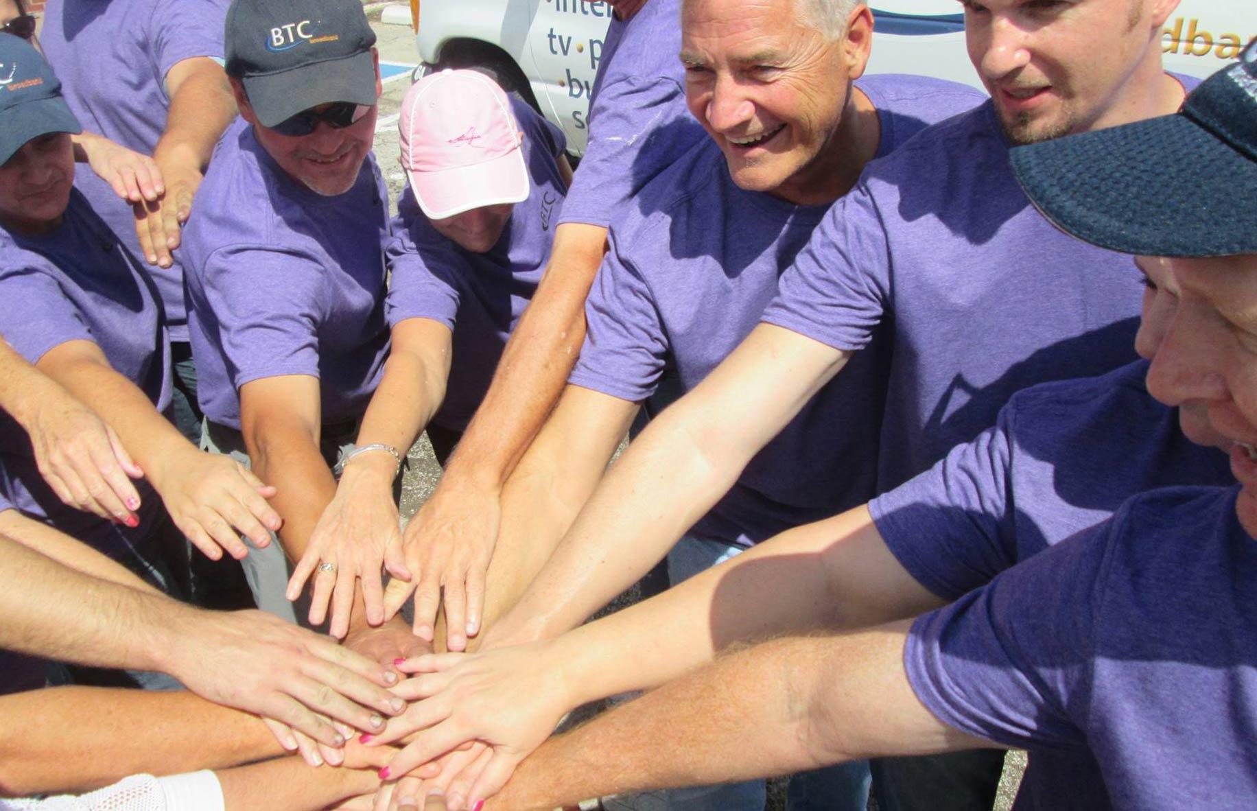 Volunteers with hands together.
